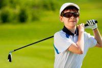 Niño con gafas de sol juega al golf