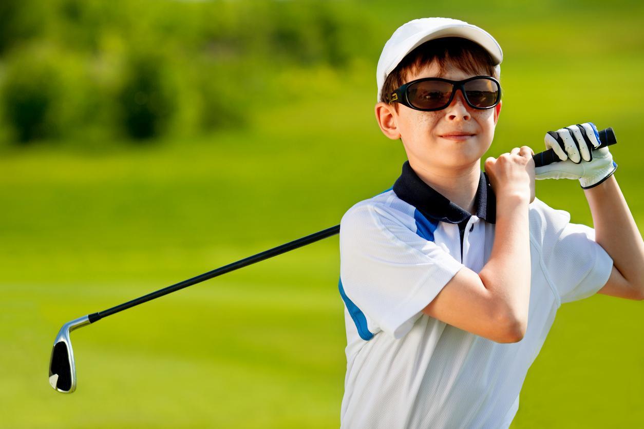 Niño con gafas de sol jugando al golf