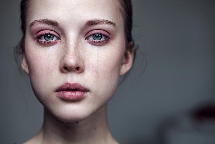 Mujer de ojos azules con los ojos rojos y lágrimas