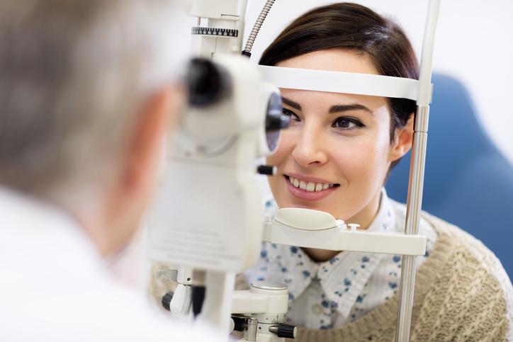 Mujer castaña con camisa de flores en consulta de oftalmología