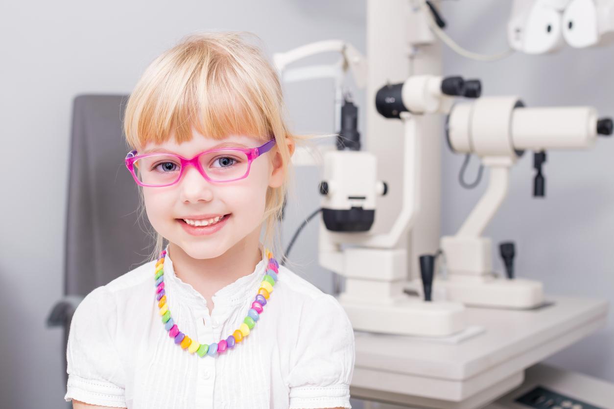 Niña rubia con gafas rosas en una consulta de oftalmología