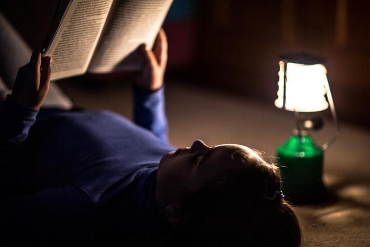 Mujer leyendo un libro a la luz de una lámpara de gas