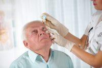 Enfermera con guantes le echa colirio de tropicamida a un paciente