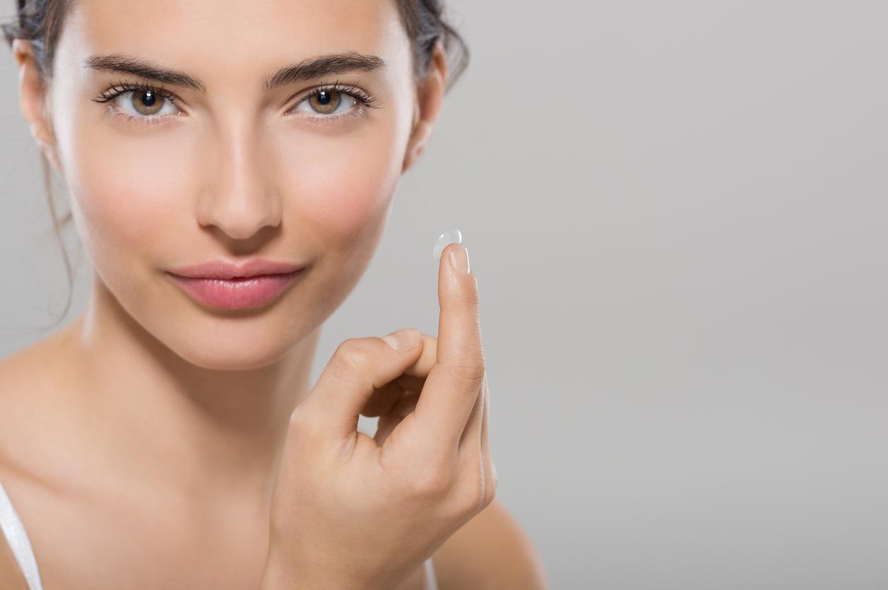 Mujer de ojos marrones sujetando una lentilla
