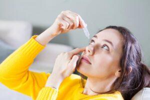 Mujer con jersey amarillo echándose lágrimas artificiales