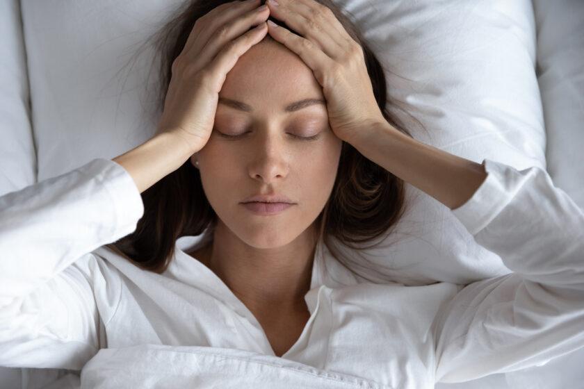 Chica en la cama tocándose la cabeza