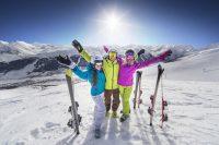 Dos mujeres y un hombre con ropa de esquí en la nieve