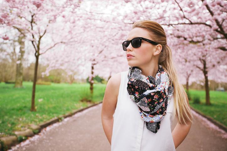 Mujer con gafas de sol en un camino de un parque con árboles en flor