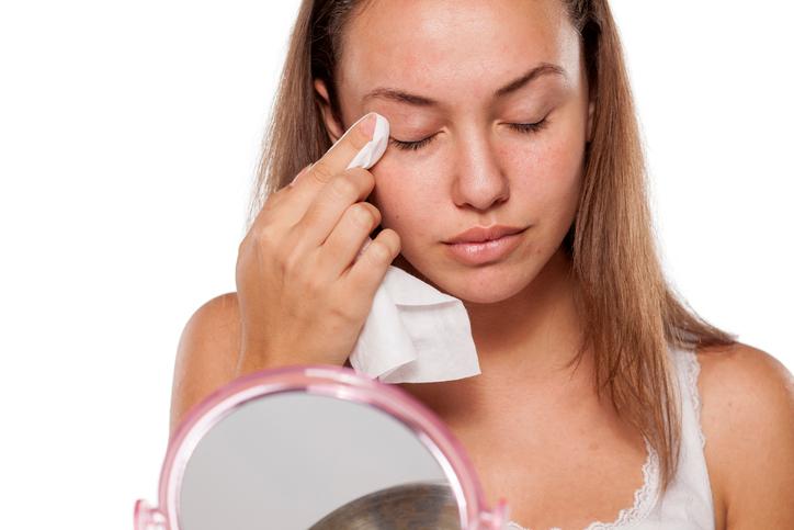 Mujer se desmaquilla frente a un espejo
