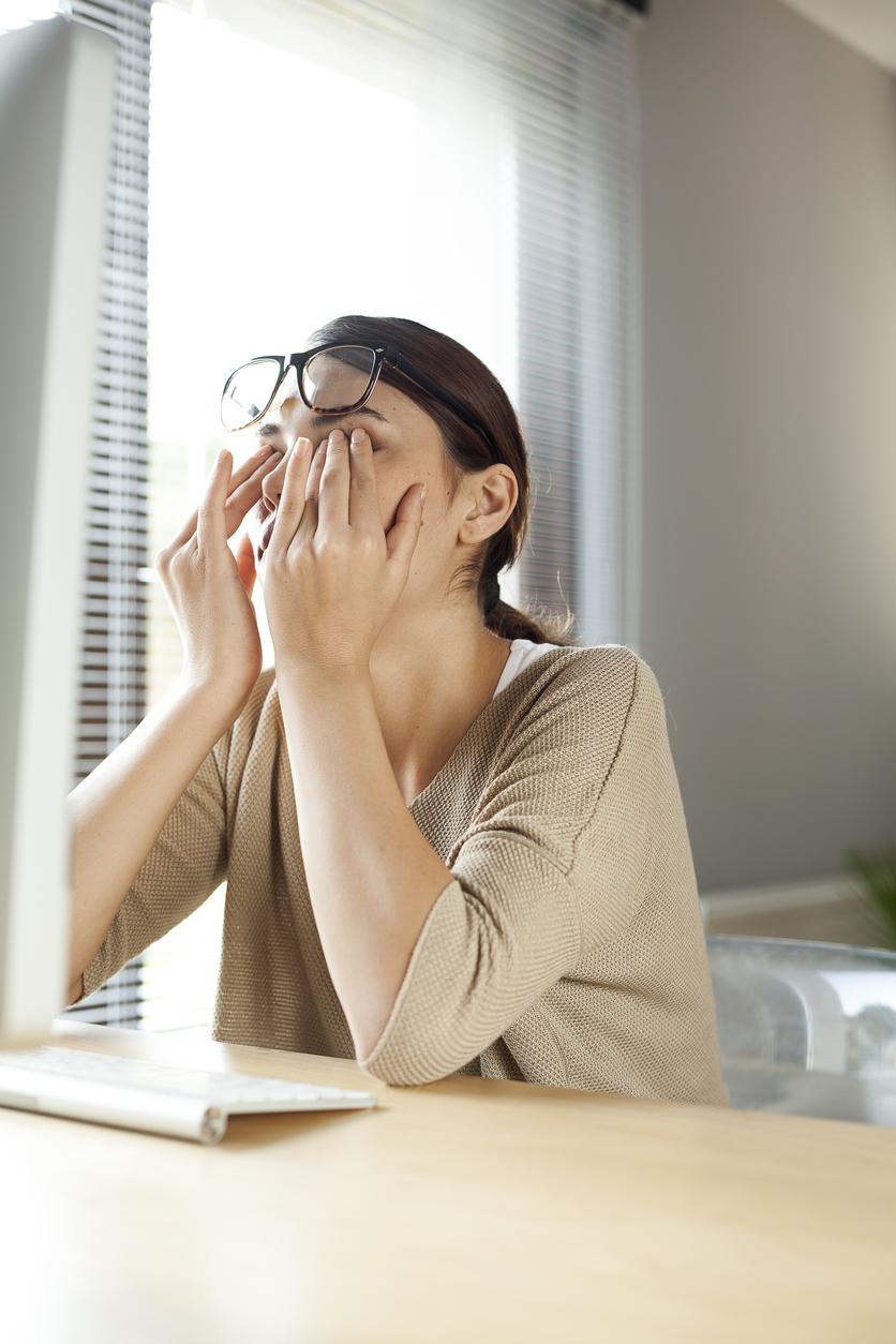Mujer de jersey beige se frota los ojos y se levanta las gafas