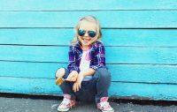 Niña con gafas de sol sentada frente a pared azul