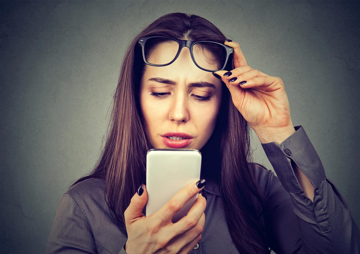 Mujer levantándose las gafas para mirar el móvil