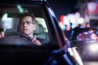 Hombre con gafas conduciendo un coche negro
