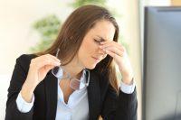 Mujer con americana negra y camisa se quita las gafas y se frota los ojos