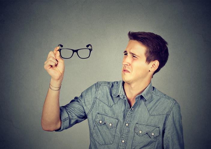 Hombre con camisa vaquera mira unas gafas negras