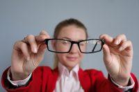 Mujer con chaqueta roja aleja las gafas para ver