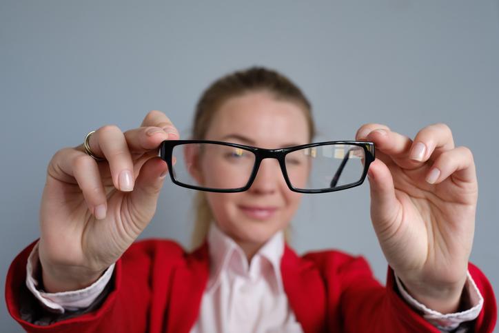 Mujer con chaqueta roja enseñando unas gafas negras