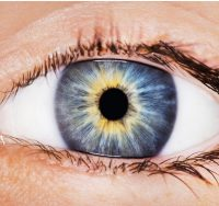 Primer plano ojo azul con reflejos amarillos