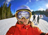 Mujer esquiando con pista al fondo