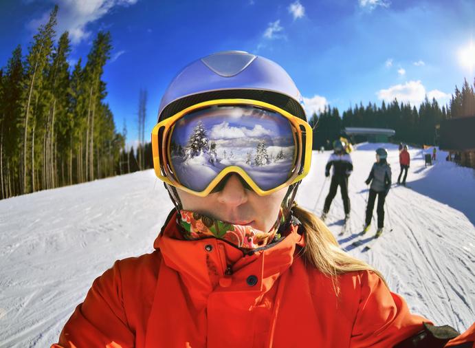 Esquiadora con grandes gafas para la nieve y chaqueta roja