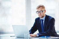 Hombre con traje y gafas trabajando en ordenador