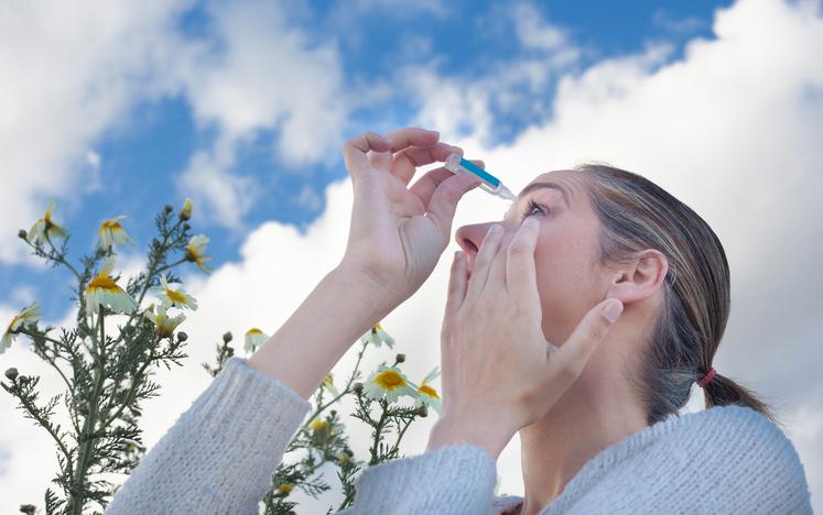 Mujer con jersey gris echándose lágrimas artificiales en el ojo