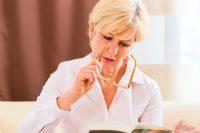 Mujer rubia poniéndose las gafas para leer una revista
