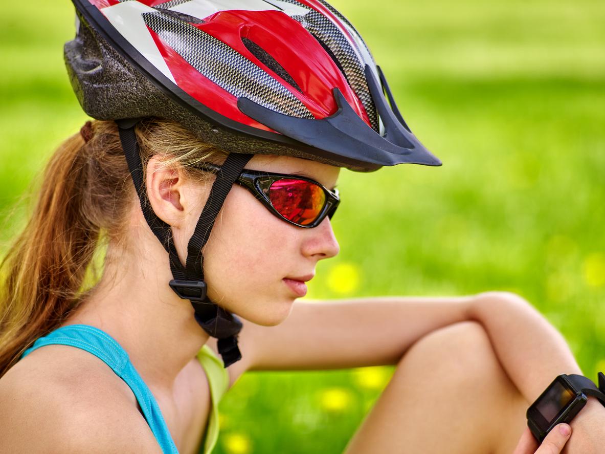 Mujer ciclista con casco y gafas