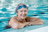Mujer en borde de piscina con gafas de nadar