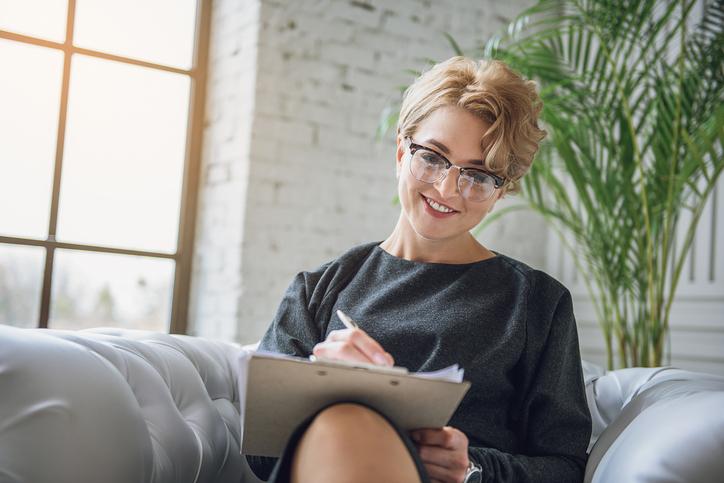 Mujer con gafas escribiendo sentada en un sofá