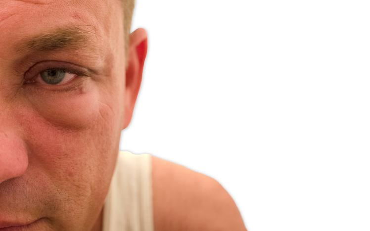 Primer plano ojo de hombre con camiseta de tirantes blanca