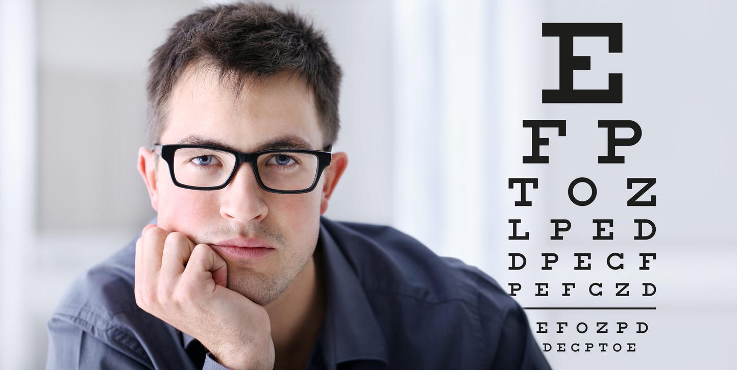Hombre con gafas negras frente a optotipo