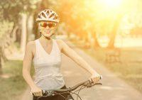 Mujer con gafas y casco montando en bicicleta