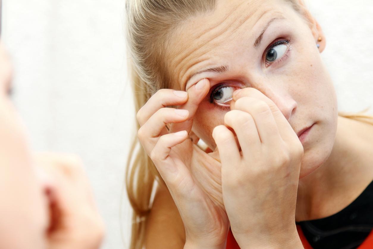 Mujer rubia de ojos azules quitándose las lentillas