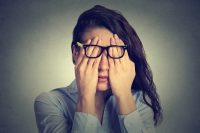 Mujer morena con gafas se frota los ojos