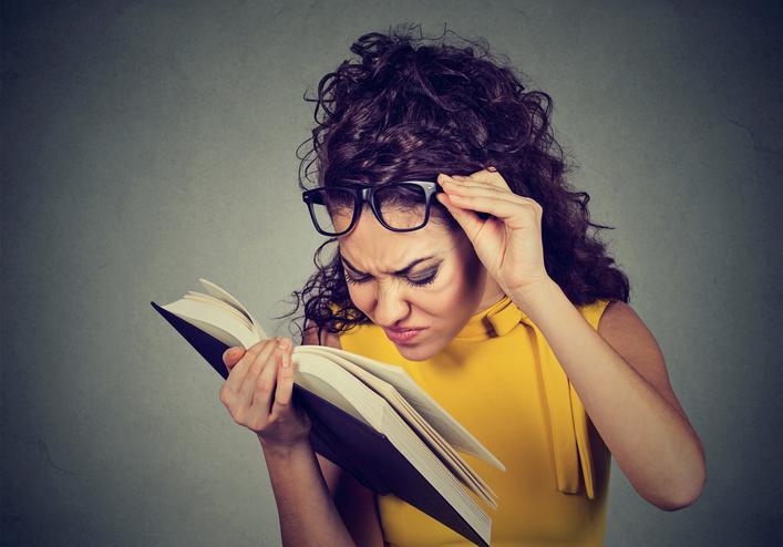 Mujer de pelo rizado se levanta las gafas para leer