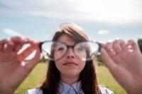 Mujer con camisa mirando a través de gafas