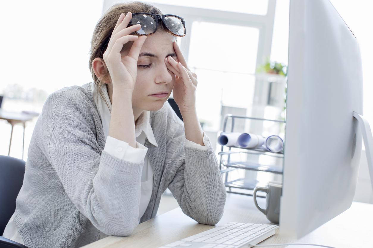 Mujer con jersey gris se frota los ojos frente al ordenador