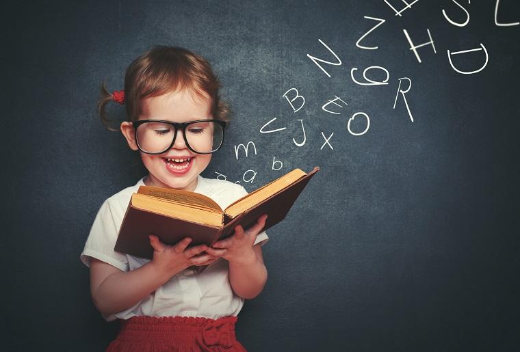 Niña con coletas y grandes gafas leyendo un libro