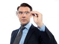 Hombre con traje mirando a través de unas gafas que tiene en la mano