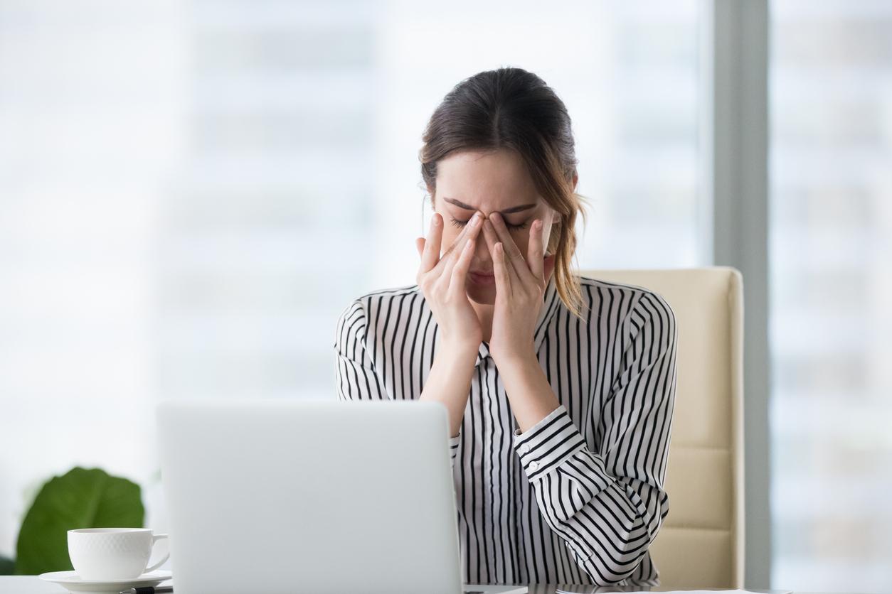 Mujer trabajando delante de un ordenador se frota los ojos