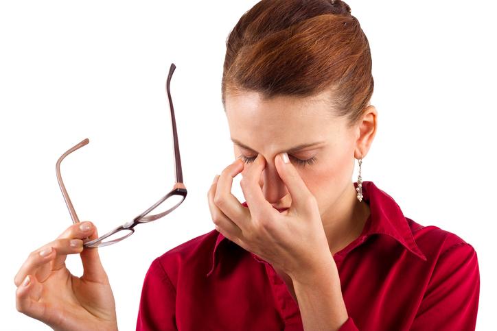 Mujer con camisa roja frotándose los ojos