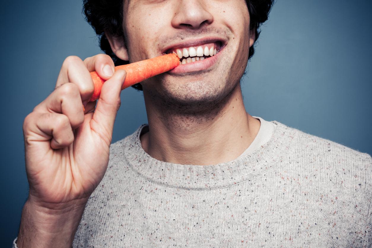 Hombre con jersey beige comiéndose una zanahoria