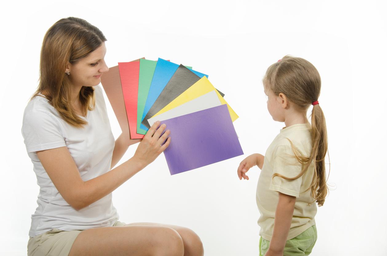 Mujer enseñando unas cartulinas de colores a una niña