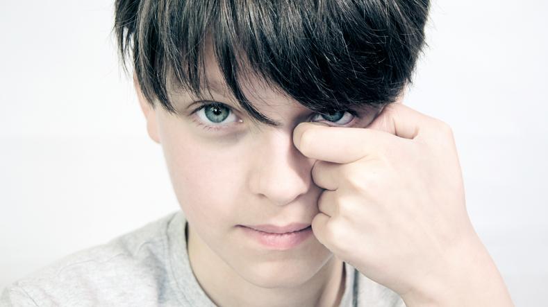 Niño moreno con ojos verdes rascándose un ojo