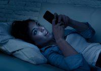 Mujer acostada mirando un móvil en la oscuridad