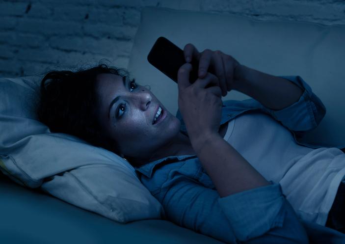 Mujer mirando el móvil en la oscuridad