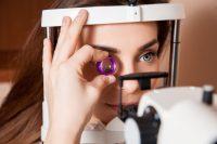 Mujer morena con ojos azules y oftalmoscopio indirecto
