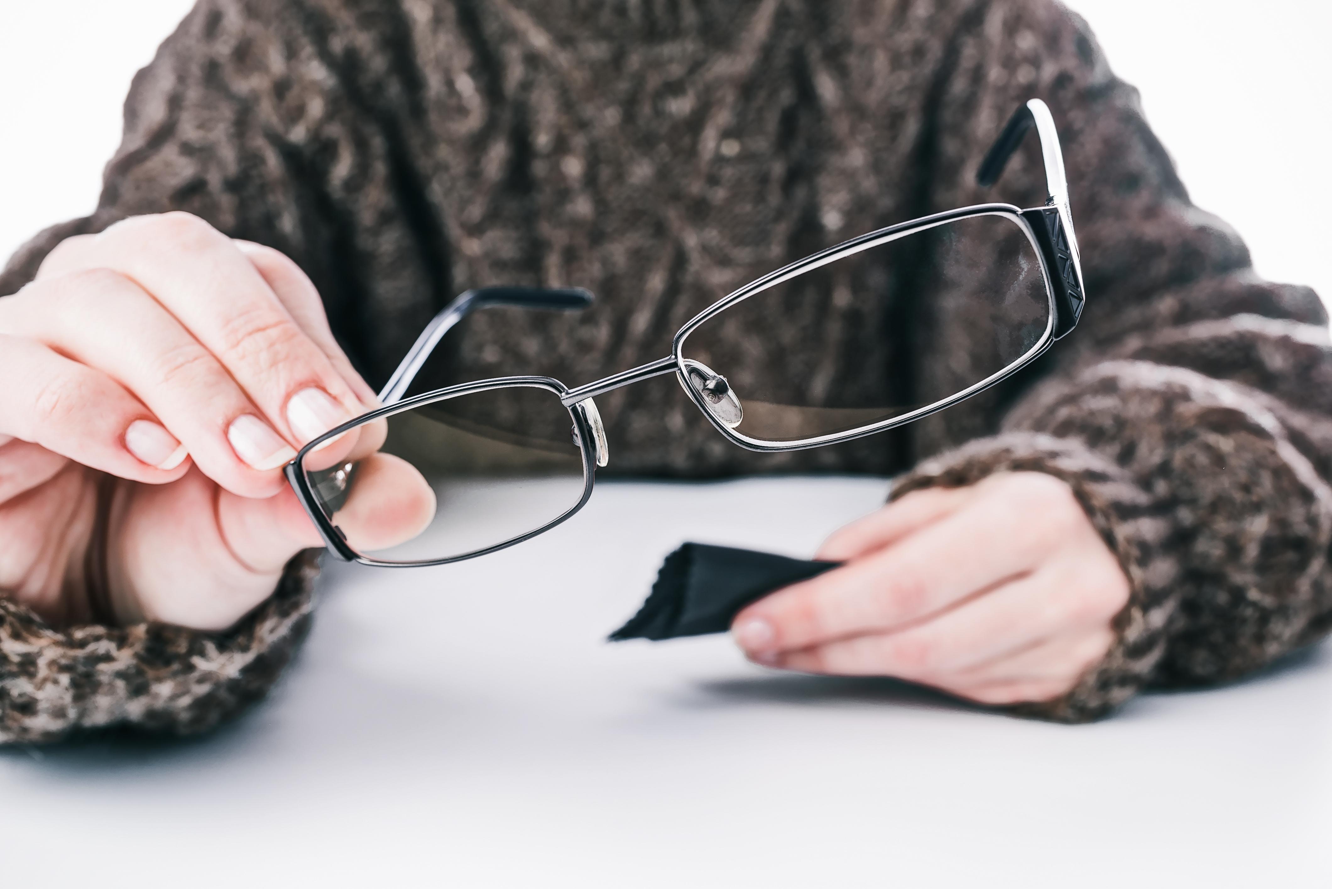 Persona con jersey marrón limpiando unas gafas