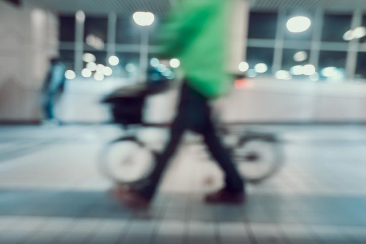 Visión borrosa de un hombre con camisa verde y bicicleta